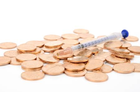 paid medicine: Coins and syringe Stock Photo