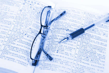 Book and pen with glasses photo