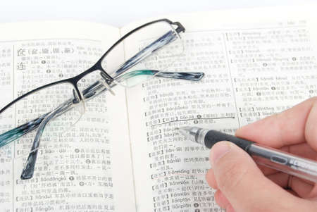 Eyeglasses and pen with dictionary photo