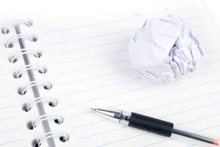Crumpled paper ball and notepad with pen photo