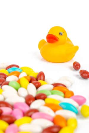 agachado: Pato de goma con los caramelos Foto de archivo