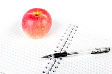 Apple,glasses and pen on notepad photo