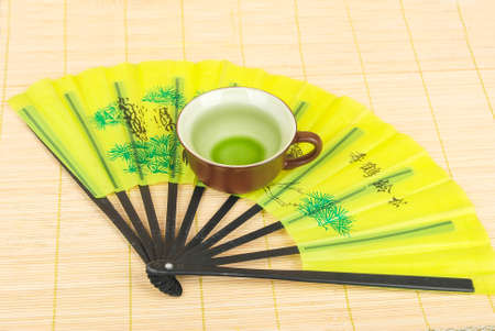 A chinese fan with tea on mat photo