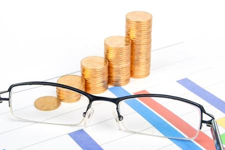 Coins and eyeglasses on trend graph photo