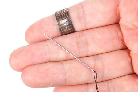 Thread,needle and thimble on white background photo