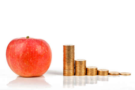 Apple and coins on white background photo