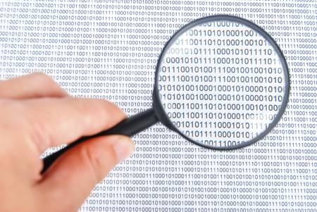 snoop: Magnifier on binary code page Stock Photo