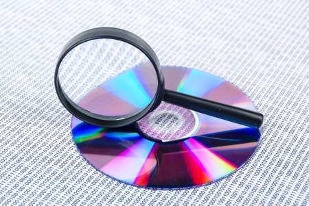 scrambling: Magnifying glass with DVD Stock Photo