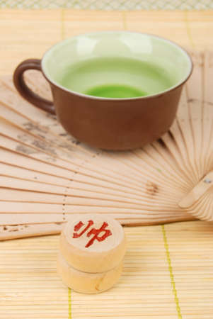 Tea,chinese fan with chess on bamboo tray photo