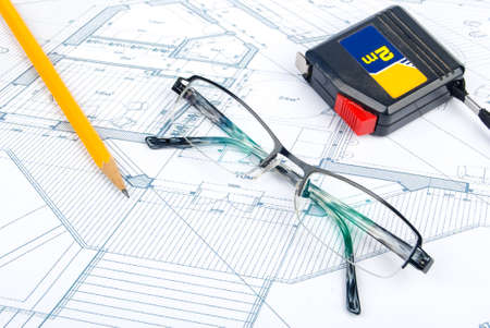 Steel tape,pencil and glasses on blueprint photo