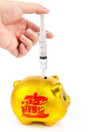 Syringe with piggy bank photo