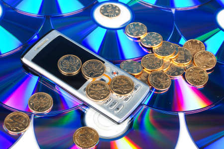 Mobilephone on DVD with coin Stock Photo - 13997677
