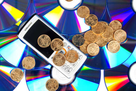 Mobilephone on DVD with coin Stock Photo - 13997679