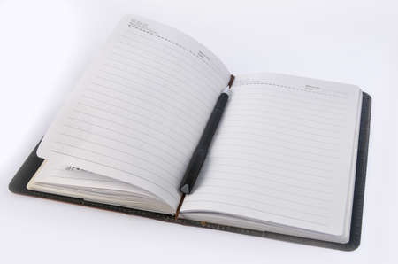 Cahier et un stylo sur fond blanc