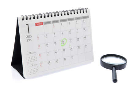 Desk Calendar and magnifier isolated on white photo