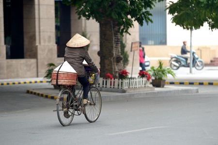ciclos: Una mujer ciclos en su bicicleta en Vietnam, el desenfoque de movimiento Editorial