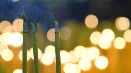 Close up of burning incense sticks with smoke and bokeh