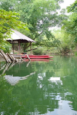 man Kayaking in green river near raft and house Stock Photo