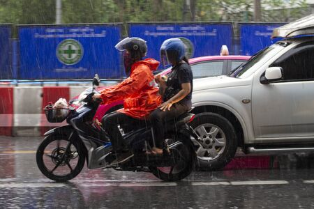 It rains on the city on streets with cars and motorcycles.