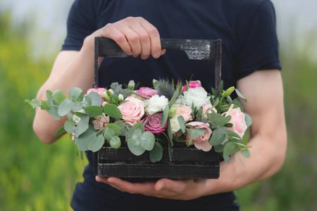 Image en gros plan d'un bel arrangement de mariage de fleurs dans une boîte en bois avec des roses roses en spray, succulentes, eustoma, hypericum blanc, eucaliptus dans les mains d'un homme Banque d'images
