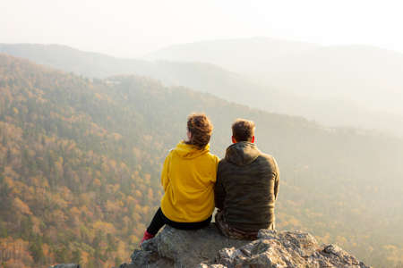 Couple in love sitting at the top of the mountain and watching autumn landscape. Sunset