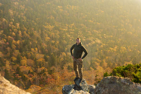 happy man standing at the top of the mountain. Landscape view of misty autumn mountain hills and man silhouette Фото со стока