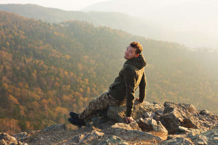 Young and happy man sitting at the top of the mountain. Landscape view of misty autumn mountain hills and man silhouette