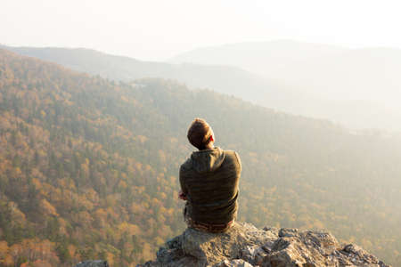 Portrait of happy man at the top of the mountain. Landscape view of misty autumn mountain hills and man silhouette