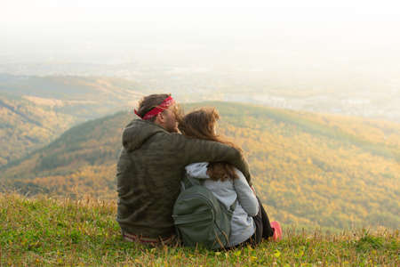 Beautiful Couple in love sitting at the top of the mountain back to the camera and watching autumn landscape at sunset Фото со стока