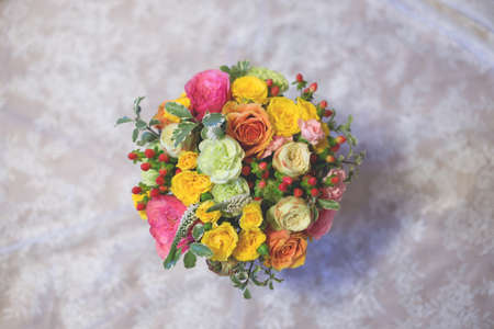 Close up of colorful bouquet in hands of florist in blue dress. Brightful and fresh mixed flowers bouquet with pink and white garden roses, yellow spray roses, carnations, veronica and greenery