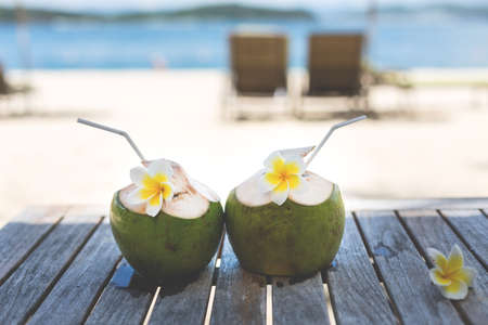 Image of Two Green coconuts and plumeria flowers or frangipani on wooden table at the seaside in summer.