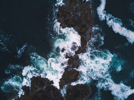 Aerial shot of waves hitting rocks Stock fotó