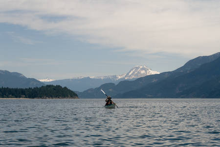Lone kayaker on water with mountains in the background