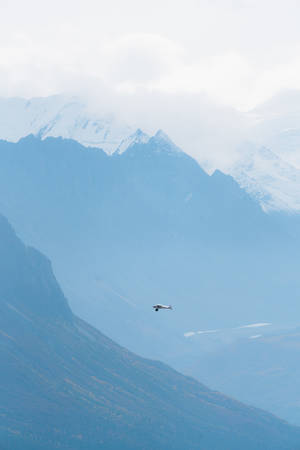 Small plane flying in remote mountains in Alaska with glaciers in the background