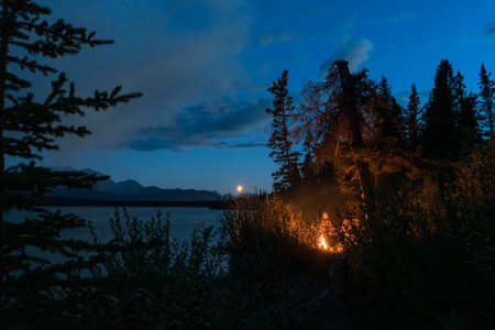 People camping with campfire next to lake in Canada at night