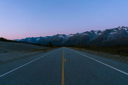 Alaskan remote mountains with half moon and pink skies after sunset during blue hour