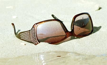 thalasso: sunglasses under sand Stock Photo