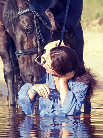A lady sitting in the water with a horse photo