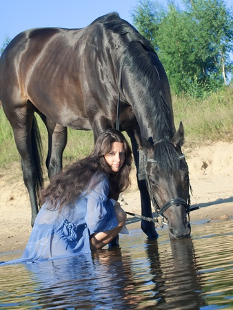 pretty women with horse in water  photo