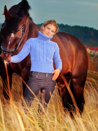 women with her horse at fall evening in the field Stock Photo - 11218306