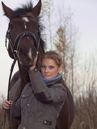 women with her horse at evening  photo
