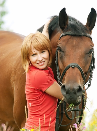 beautiful blond with  horse in field photo