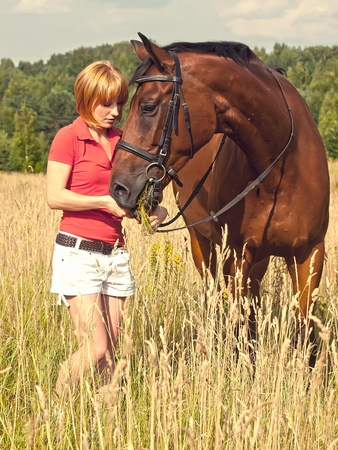 young girl  with her horse in field photo