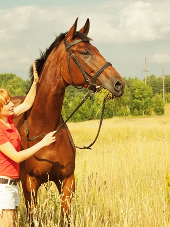 young cute girl  with her horse outdoor sunny day photo