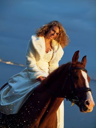 bride ride on red  horse in gulf at evening photo
