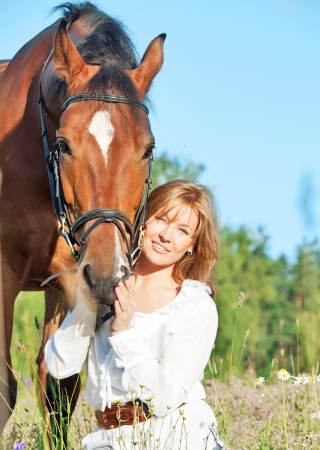 pretty women with her horse in blossom field sunny day