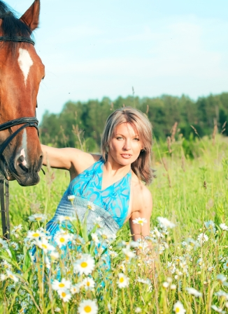 pretty women in blue dress with her horse in blossom meadow sunny evening photo