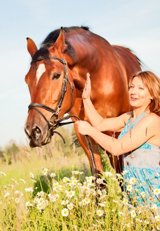 pretty women with her horse in meadow photo