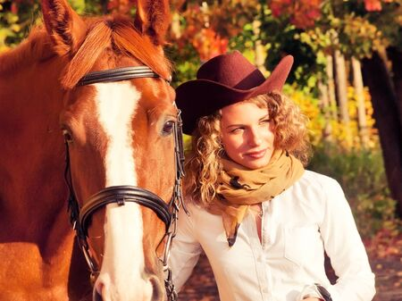 Happy cowgirl with her red horse.  Stock Photo