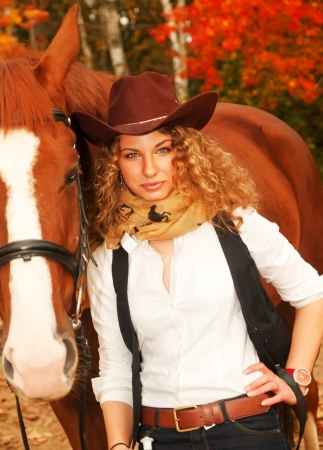 Beautiful  cowgirl with her red horse. soft focus photo